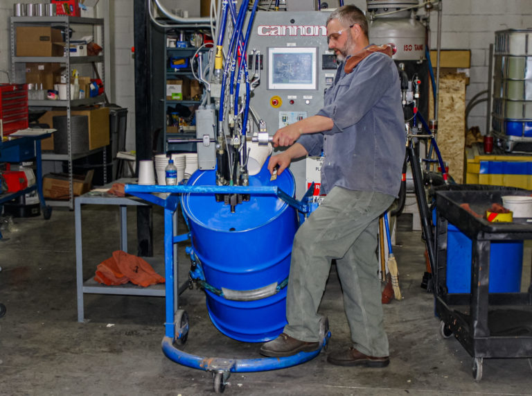 Paragon employee filling blue barrel